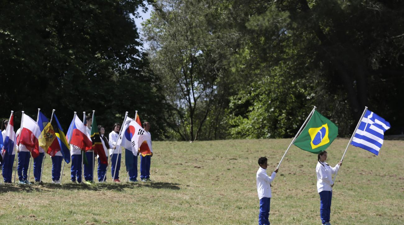 A boy and a girl hold the Brazilian and Greek, right, flags during the ceremonial lighting of the Olympic flame in Ancient Olympia, Greece, Thursday, April 21, 2016. The flame will be transported by torch relay to the Brazilian city of Rio de Janeiro, whi