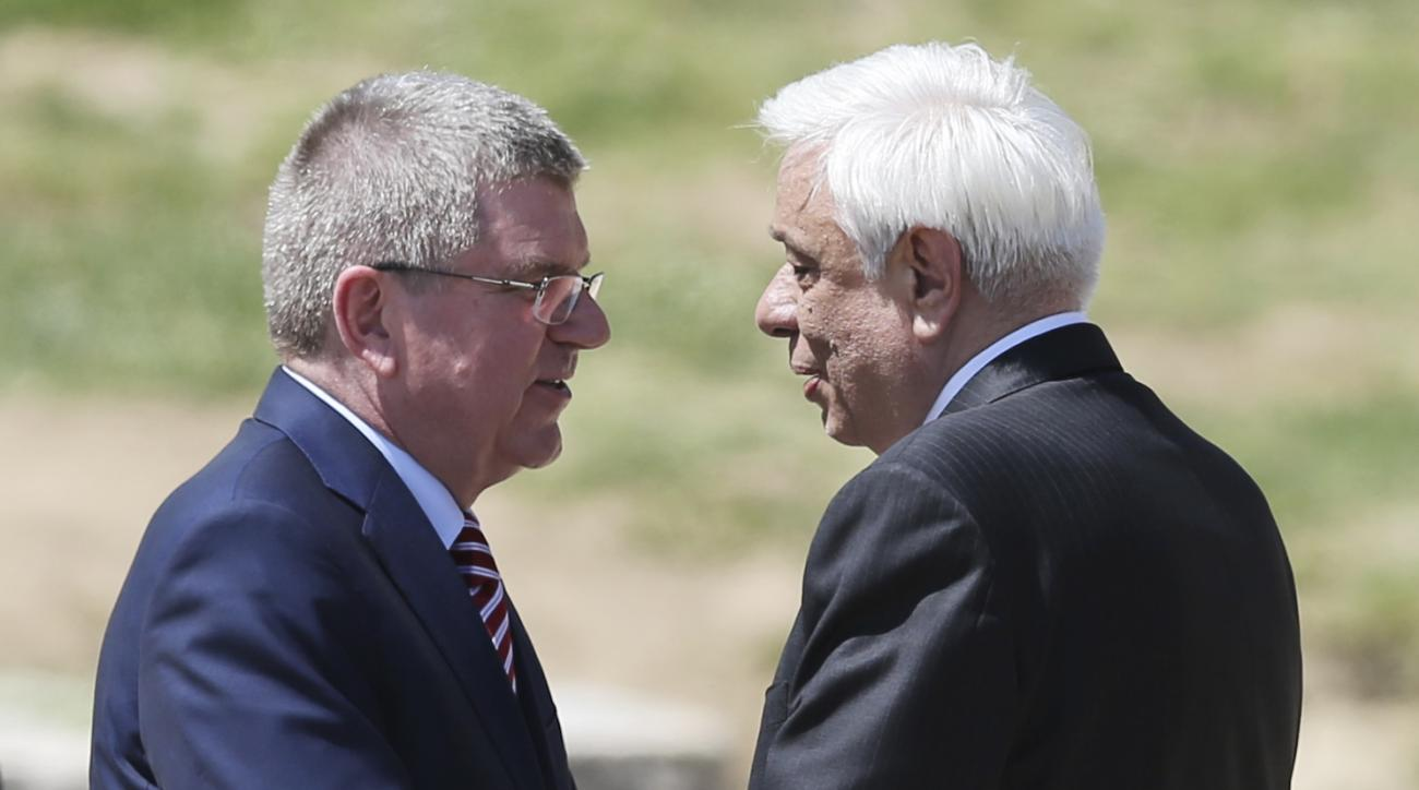 IOC President Thomas Bach chats with Greek President Prokopis Pavlopoulos, right, during the ceremonial lighting of the Olympic flame in Ancient Olympia, Greece, Thursday, April 21, 2016. The flame will be transported by torch relay to the Brazilian city