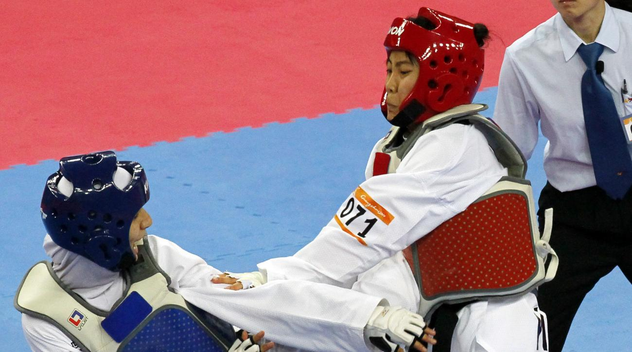 FILE - This is a Friday, Nov. 19, 2010 file photo of Raheleh Asemani of Iran, left, in action against  South Korea's Noh Eun-sil, during their women's under 62 Kg Taekwondo final at the 16th Asian Games in Guangzhou, China. The former-Iranian taekwondo fi