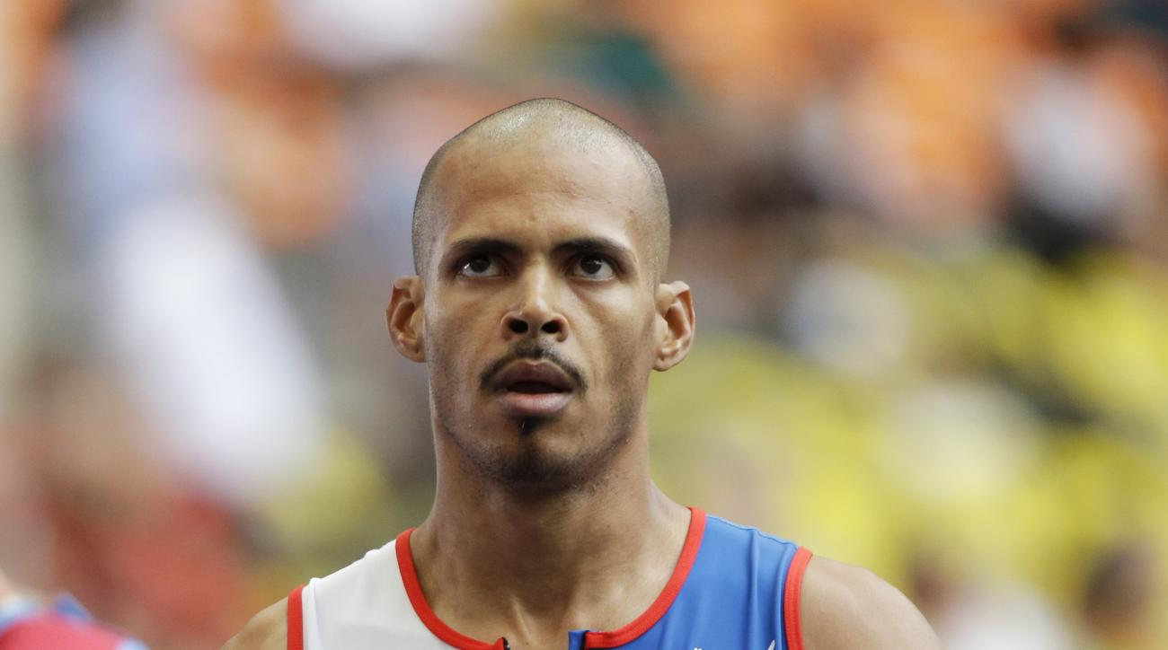 FILE - In this Aug. 12, 2013, file photo, Dominican Republic's Felix Sanchez looks at the timing board after competing in a men's 400-meter hurdles heat at the World Athletics Championships in the Luzhniki stadium in Moscow, Russia. Sanchez announced on T