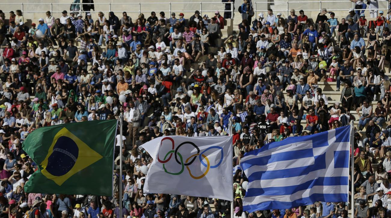 The flags of Greece, right, Brazil left, and Olympics wave as spectators wait for the handover ceremony at Panathinean stadium in Athens, Wednesday, April 27, 2016. The flame arrives in Brazil on May 3, and will be relayed across the vast country by about
