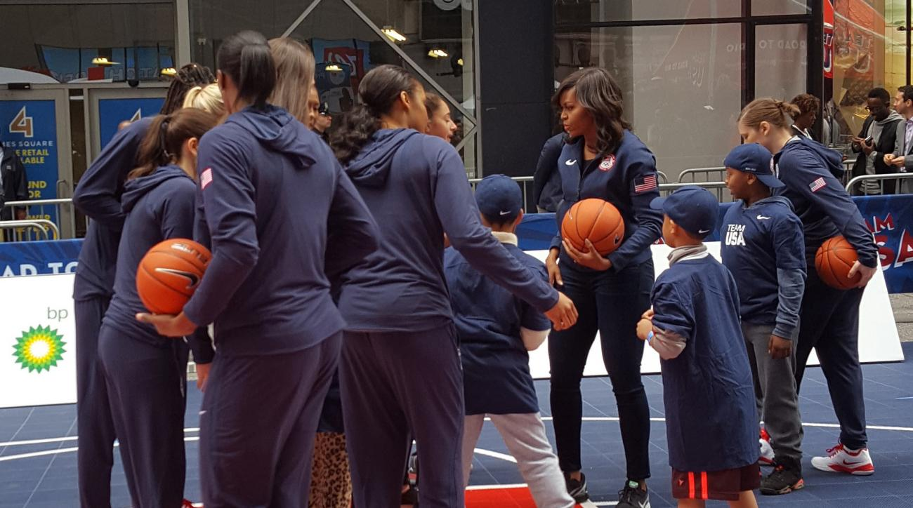 First lady Michelle Obama, fourth from right, joins members of Team USA and some children on a makeshift basketball court erected on New York City's Times Square, Wednesday, April 27, 2016. The first lady was on hand as the United States Olympic Committee