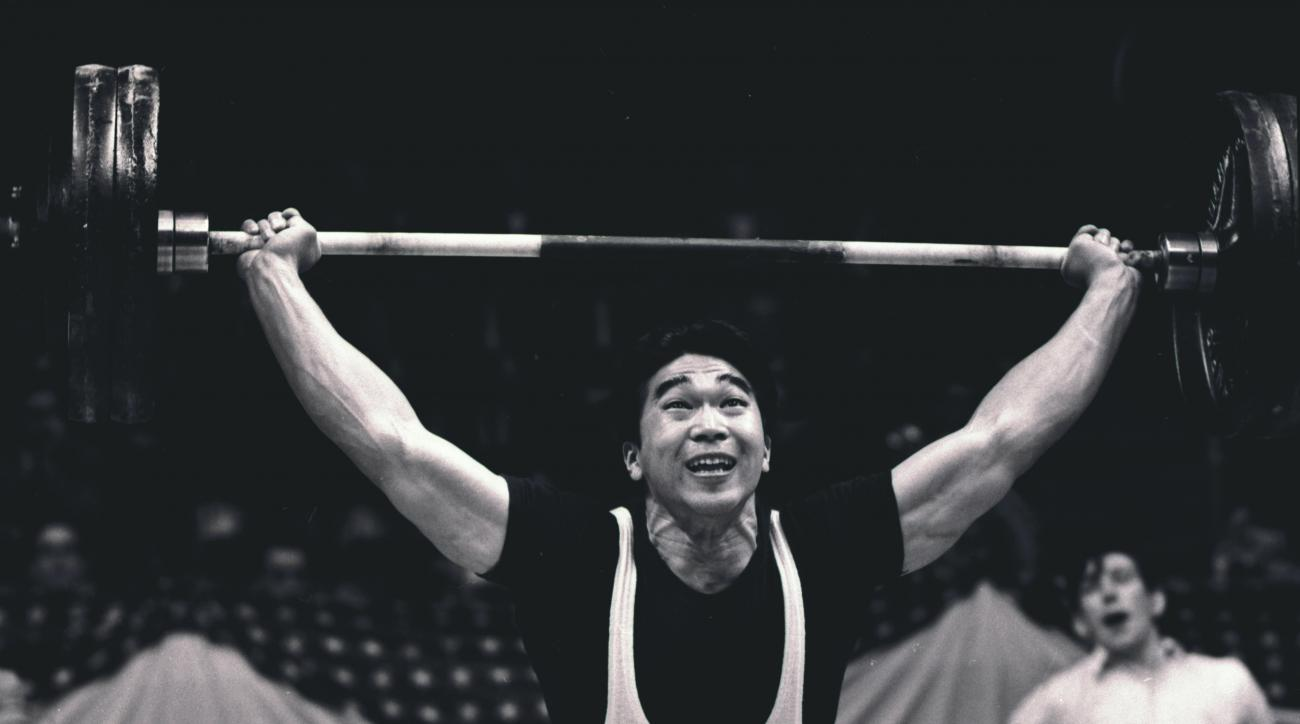 FILE - In this May 17, 1958, file photo, Tommy Kono, of the United States, competes in a weightlifting match between the U.S. team and a visiting Russian team in New York. Kono, who took up weightlifting in an internment camp for the Japanese and went on