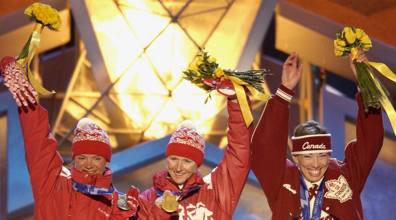 FILE - In this Feb. 15, 2002, file photo, the three Olympic medalists in the women's 5-kilometer free pursuit alpine skiing event, Russian silver medalist, Larissa Lazutina, left, Russian gold medalist Olga Danilova, center and Canadian bronze medalist Be
