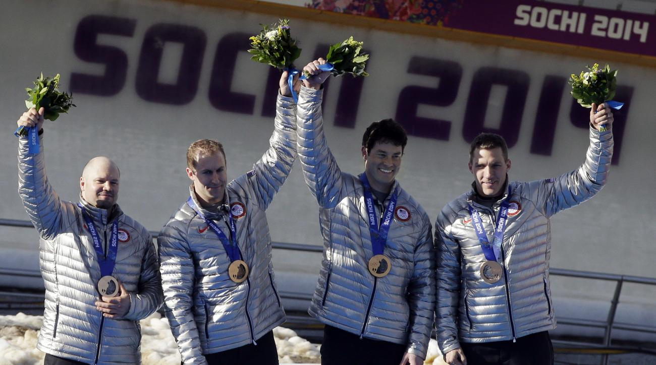 FILE - In this Feb. 23, 2014, file photo, members of the USA-1 team Steven Holcomb, left, Curtis Tomasevicz, Steven Langton and Christopher Fogt, celebrate after they won bronze in the men's four-man bobsled at the Winter Olympics in Krasnaya Polyana, Rus
