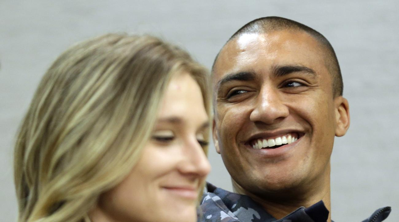 FILE - In this Feb. 18, 2016, file photo, Ashton Eaton, right, and his wife, Brianne Theisen-Eaton,  participate in a news conference in New York. Ashton hopes to defend his Olympic decathlon title at the Rio de Janeiro Games for the U.S., while Brianne g