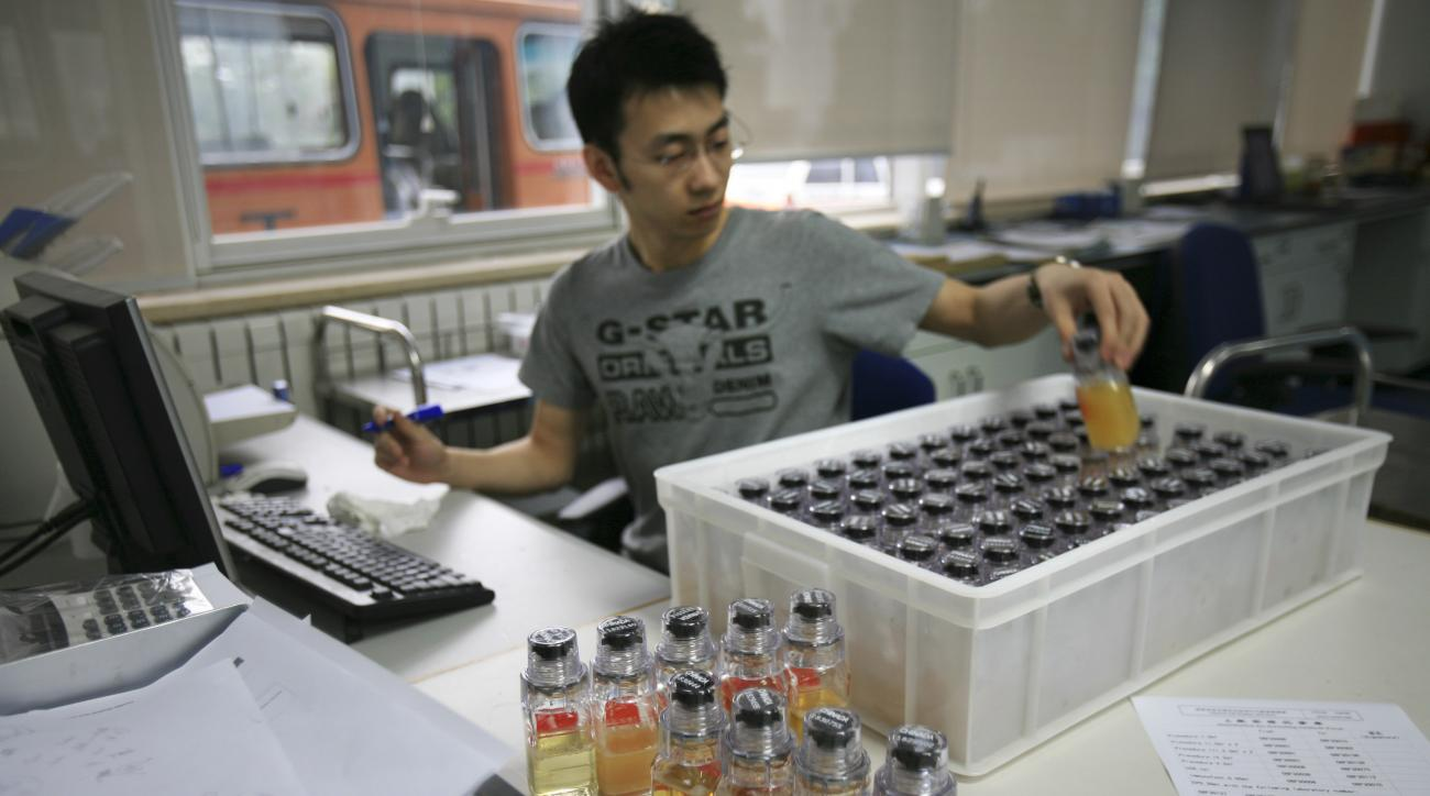 FILE - In this Monday, June 30, 2008 file photo, urine samples from Chinese athletes are recorded upon arriving at China Anti-Doping Agency in Beijing. So far, 31 unidentified athletes in six sports from 12 countries have been caught in retests of samples