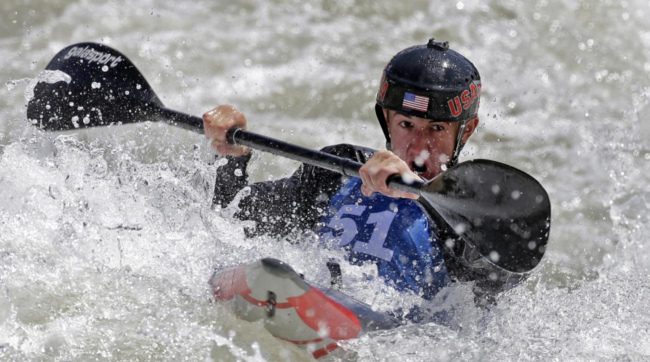 FILE - In this April 8, 2016, file phot, Michal Smolen paddles toward the finish line during the first day of the 2016 Slalom Olympic Team Trials for canoe and kayak in Charlotte, N.C. Born in Poland but living in the United States, the kayaker could've g