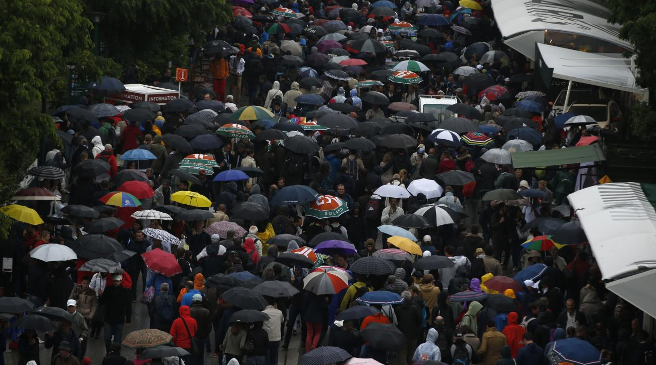 People leave the Roland Garros stadium, Monday, May 30, 2016 in Paris. French Open organizers have announced the cancellation of all matches Monday at Roland Garros because of persistent rain forecast to last all day. (AP Photo/Alastair Grant)