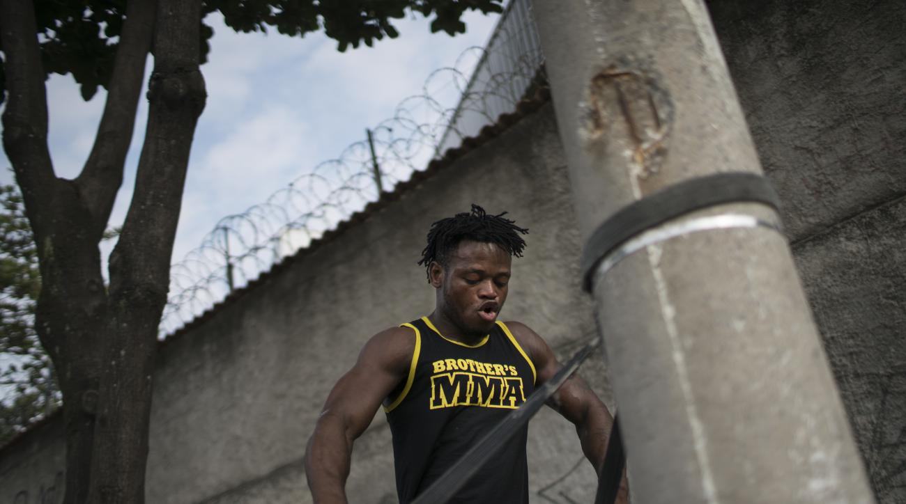 In this May 27, 2016 photo, Popole Misenga, a refugee and judo athlete from the Democratic Republic of Congo, uses a judo black belt attached to a street light pole to trains near his home in Rio de Janeiro, Brazil, in hopes of making the first Olympic re