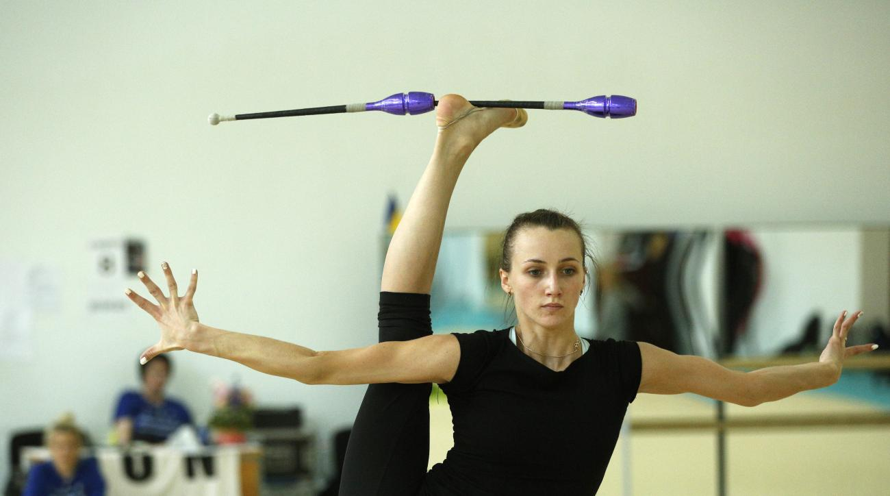 In this photo taken Tuesday, June 7, 2016, Crimean gymnast Anna Rizatdinova, who still competes for Ukraine, performs during training in Kiev, Ukraine. Two years on from Russia's annexation of Crimea, athletes from the Black Sea peninsula are split betwee