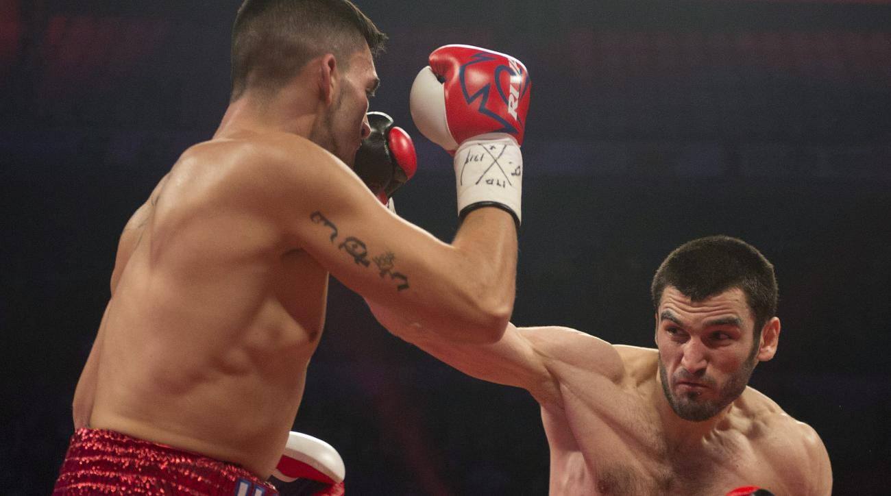 FILE - In this Dec. 19, 2014, file photo, Artur Beterbiev, right, of Russia, lands a punch on United States' Jeff Page Jr. during a light heavyweight fight in Quebec City. Unbeaten light heavyweight Artur Beterbiev is the latest professional boxer to deci
