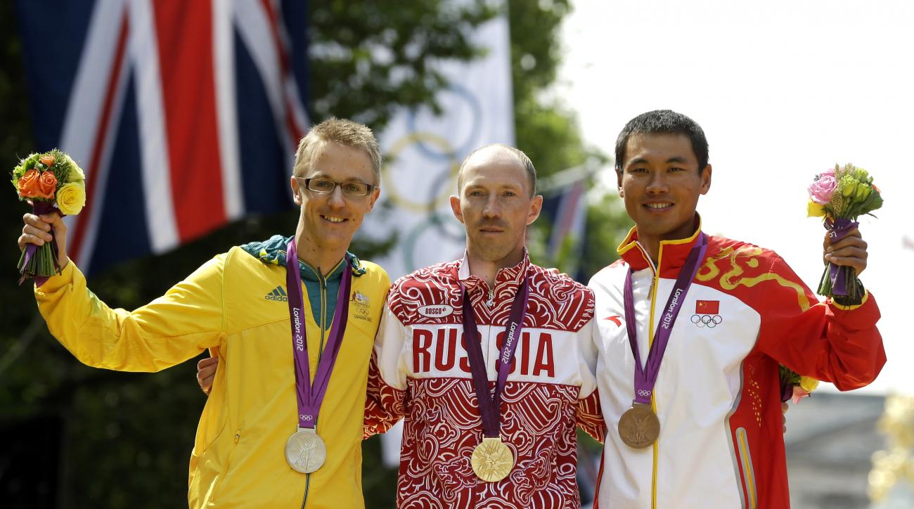 FILE - In this Aug. 11, 2012 file photo, gold-medallist Sergei Kirdyapkin of Russia, center, stands with silver-medallist Jared Tallent of Australia, left, and bronze-medallist Si Tianfeng of China after the men's 50-kilometer race walk competition at the