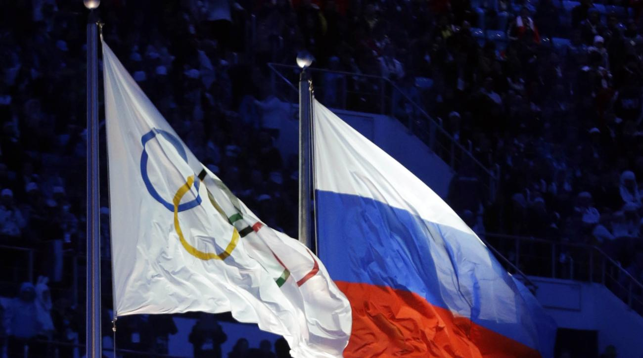 FILE - In this Feb. 7, 2014 file photo the Russian and the Olympic flags wave during the opening ceremony of the 2014 Winter Olympics in Sochi, Russia. Olympic leaders met Tuesday, June 21, 2016 to consider further steps to crack down on doping ahead of t