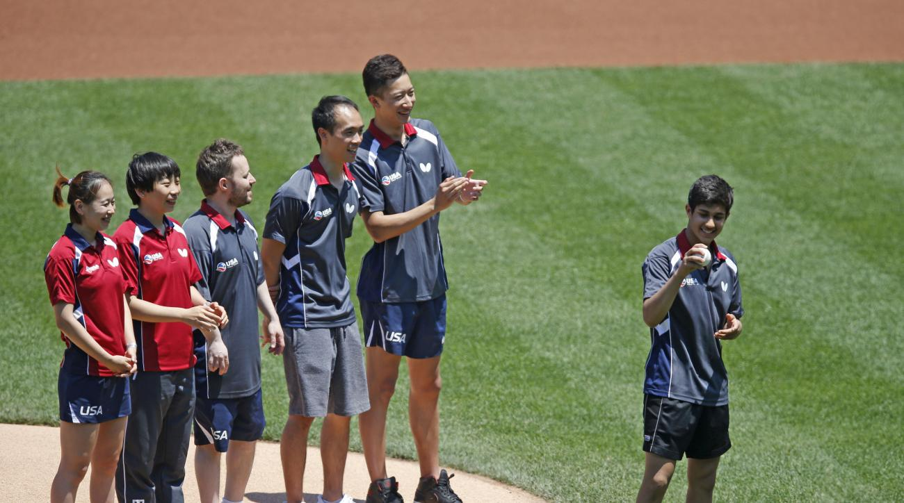 Members of the U.S. Olympic table tennis team applaud as Kanak Jha, of Milpitas, Calif., holds a baseball before throwing out a ceremonial first pitch on his 16th birthday prior to the start of a baseball game between the Atlanta Braves and the New York M