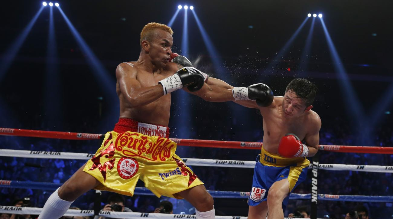File-This March 7, 2015, file photo shows China's double Olympic gold medalist Zou Shiming, right, and Thailand's Amnat Ruenroeng exchanging punches during their IBF flyweight title belt boxing match at the Venetian Macao in Macau.  Ruenroeng and Cameroon