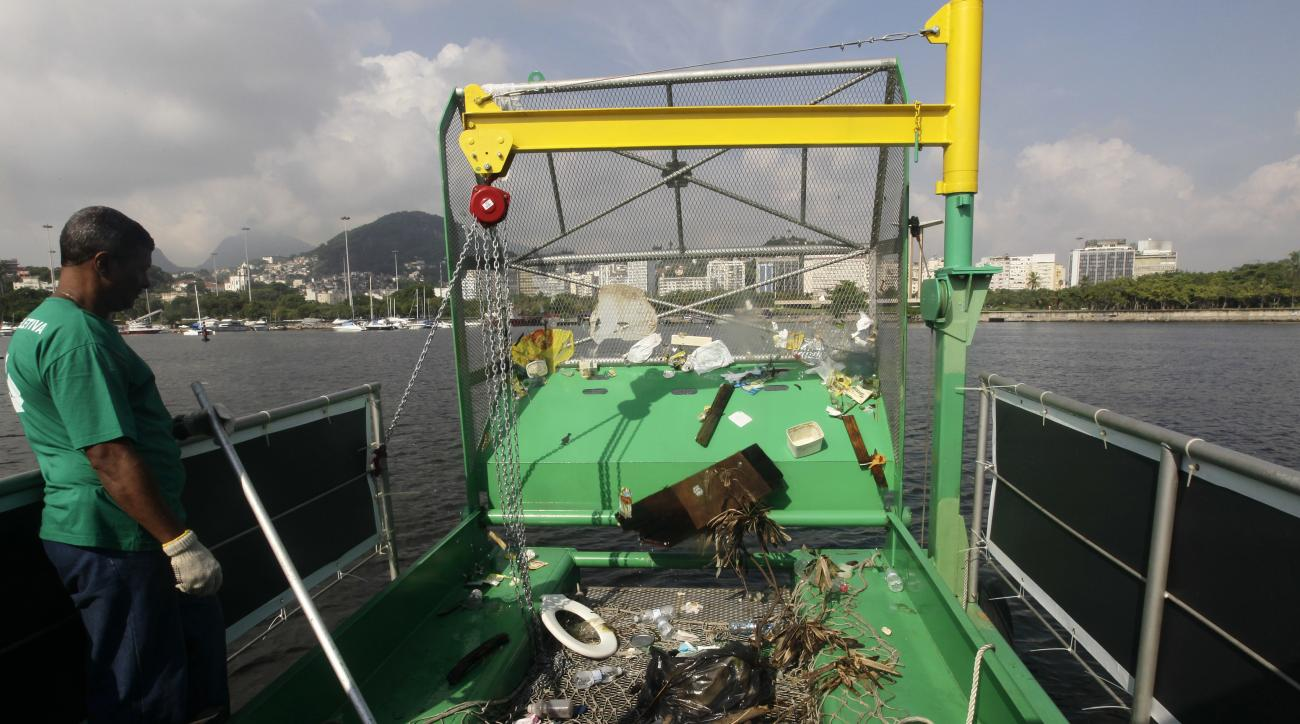 FILE - In this Jan. 6, 2016 file photo, a worker stands next to trash collected by a garbage-collecting barge in Guanabara Bay in Rio de Janeiro, Brazil. The head of World Sailing said in an interview on Wednesday, July 6, 2016 that the  boats will be cri