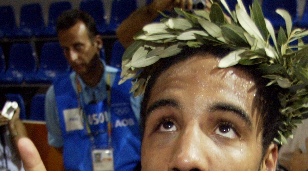 FILE - In this Aug. 29, 2004, United States Andre Ward, from Oakland, Calif., gestures No. 1 and shows off his gold medal to the fans after an awarding ceremony of the light heavyweight boxing in the 2004 Athens Olympic Games at the Peristeri boxing hall