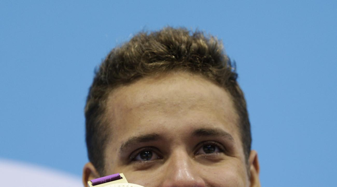 FILE - In this Tuesday July 31, 2012 file photo, South Africa's Chad le Clos poses with his gold medal for the men's 200-meter butterfly swimming final at the Aquatics Centre in the Olympic Park during the 2012 Summer Olympics in London. South African Oly