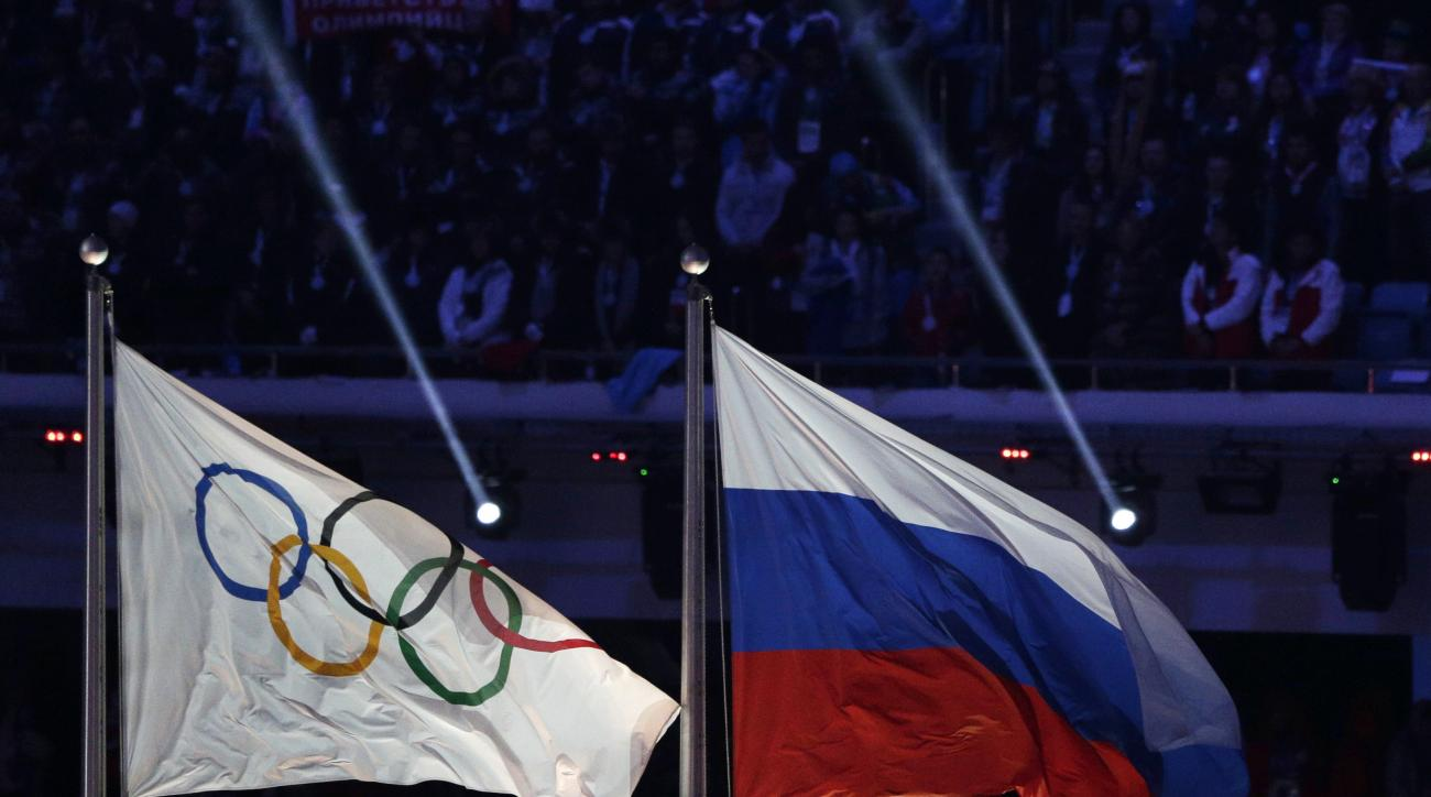 FILE- In this Feb. 23, 2014, file photo, the Russian national flag, right, flies after next to the Olympic flag during the closing ceremony of the 2014 Winter Olympics in Sochi, Russia. The World Anti-Doping Agency commissioned an investigation, being hea