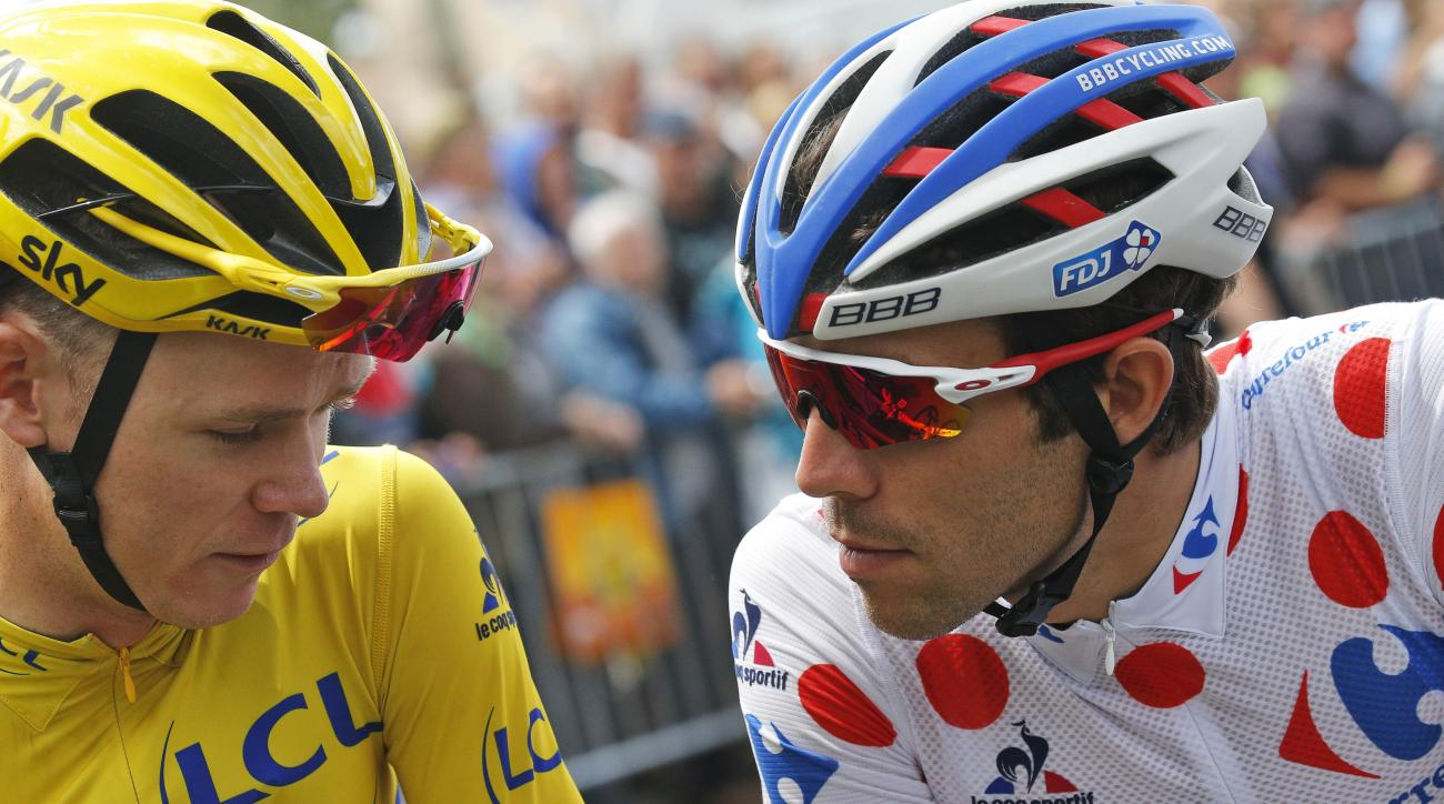 Britain's Chris Froome, wearing the overall leader's yellow jersey, and Thibaut Pinot of France, wearing the best climber's dotted jersey, talk prior to the start of the eleventh stage of the Tour de France cycling race over 162.5 kilometers (100.7 miles)