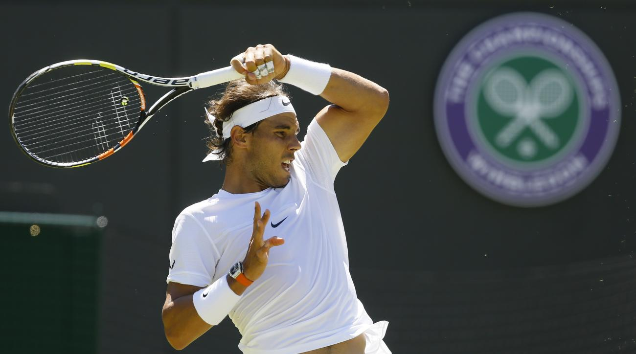 FILE - In this Tuesday, June 30, 2015 file photo, Rafael Nadal of Spain returns a ball to Thomaz Bellucci of Brazil during their singles first round match at the All England Lawn Tennis Championships in Wimbledon, London.  Nadal has pulled out of this yea