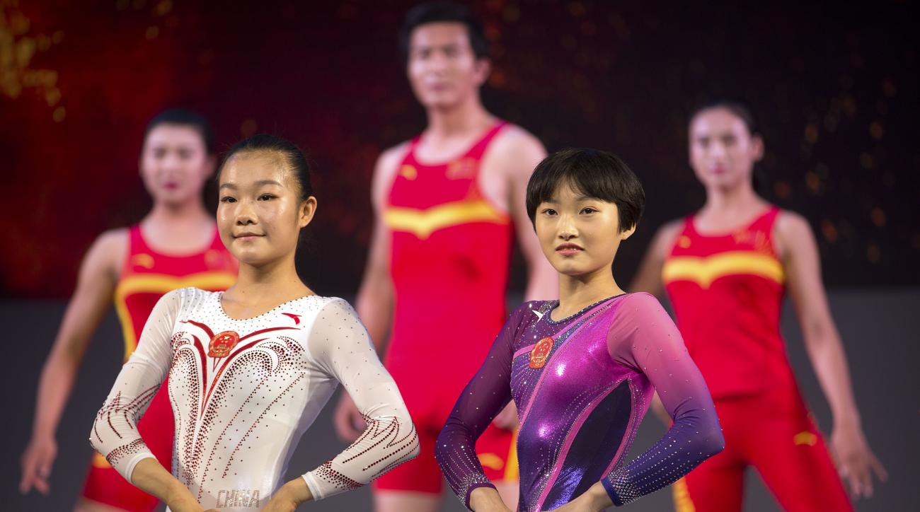 FILE - In this Wednesday, June 29, 2016 file photo, models pose in Chinese team uniforms for different sports during an event to unveil the official Team China 2016 Rio Olympics team uniforms at the Water Cube in Beijing. China is sending 416 athletes in
