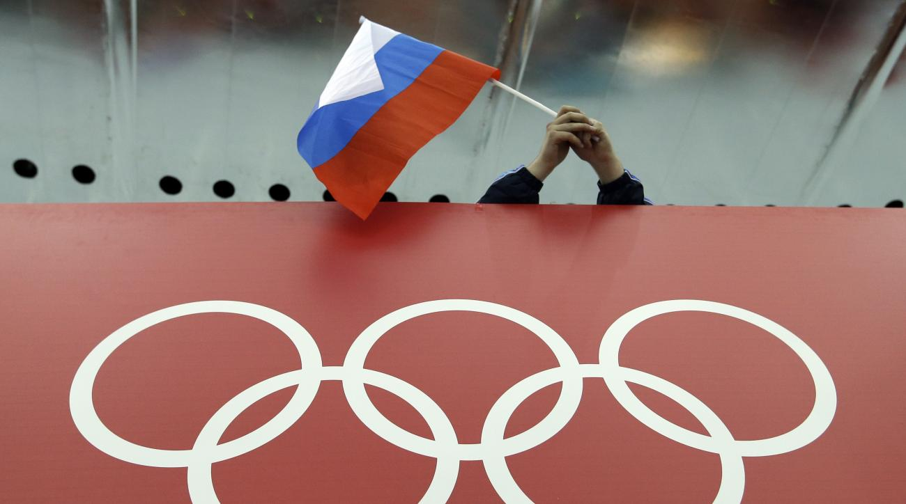 FILE - In this Feb. 18, 2014, file photo, a Russian skating fan holds the country's national flag over the Olympic rings before the start of the men's 10,000-meter speedskating race at Adler Arena Skating Center during the 2014 Winter Olympics in Sochi, R