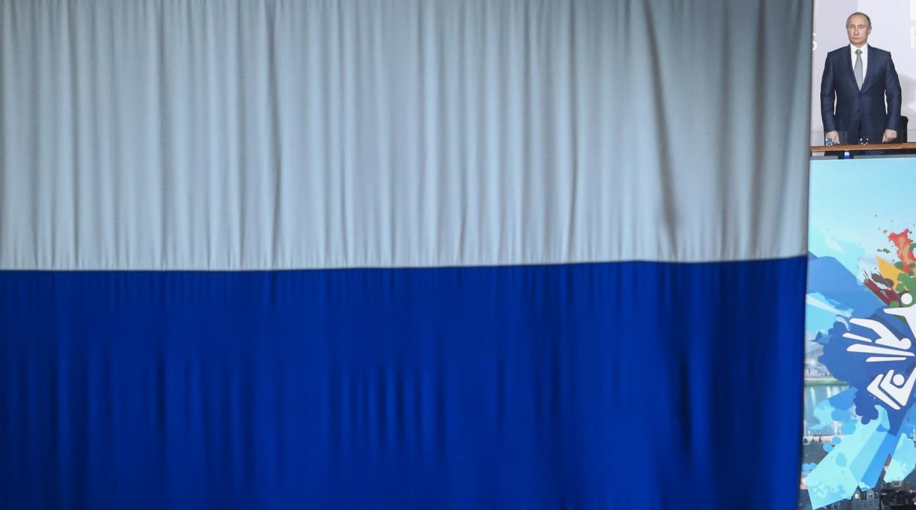 FILE - In this July 24, 2015 file photo Russian President Vladimir Putin is seen at right next to the Russian national flag as he listens to the anthem of Russia during the opening ceremony at the Swimming World Championships in Kazan, Russia. On Monday,
