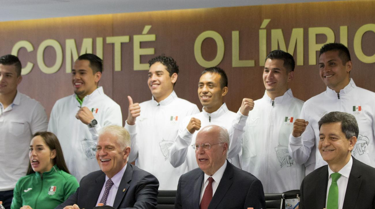 Athletes from Mexico's Olympic delegation pose with Carlos Padilla Becerra, seated center left, president of Mexico's olympic committee; Secretary of Health Dr. Jose Narro Robles, seated center right; and Pablo Kuri Morales, seated right, Mexico's subsecr