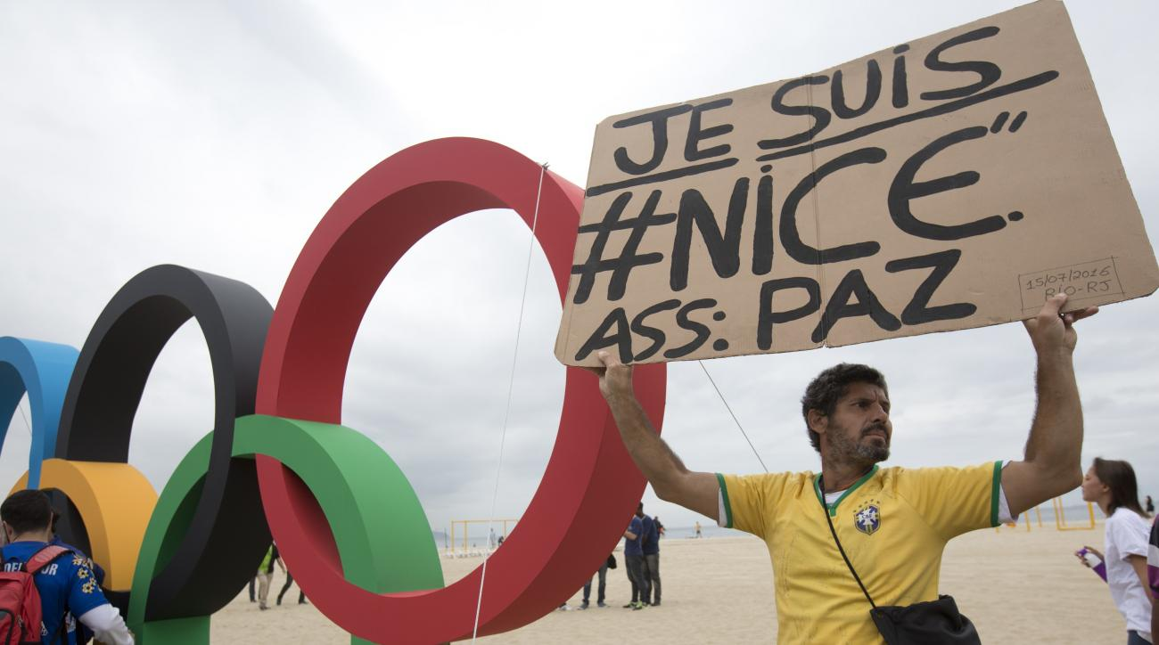 A man holds a sign to show solidarity with Nice during the presentation of Olympic rings made from recycled material, at Copacabana beach in Rio de Janeiro, Brazil, Thursday, July 21, 2016. Brazilian police arrested 10 people who allegedly pledged allegia