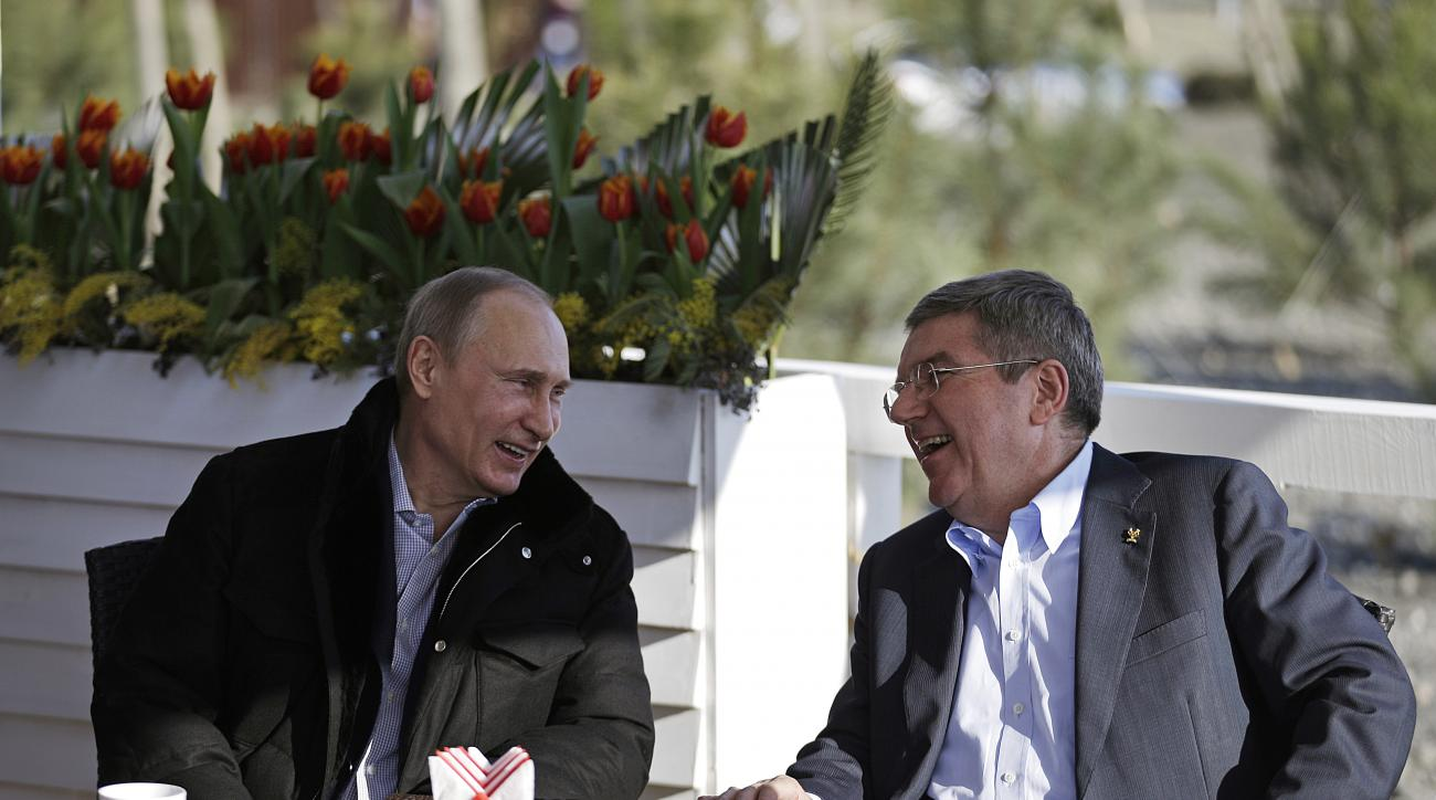 FILE - In this Feb. 15, 2014 file photo Russian President Vladimir Putin, left, and International Olympic Committee President Thomas Bach sit at a cafe along the promenade on the Black Sea near the Olympic Park at the 2014 Winter Olympics in Sochi, Russia