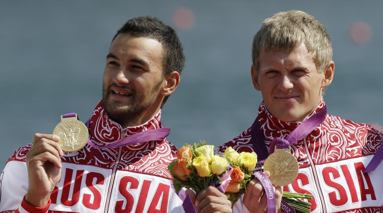 Russia's  Yury Postrigay, right, and Alexander Dyachenko show the gold medals they won in the men's kayak double 200m in Eton Dorney, near Windsor, England, at the 2012 Summer Olympics, Saturday, Aug. 11, 2012. (AP Photo/Natacha Pisarenko)
