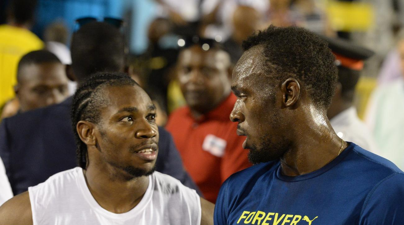 FILE - In this June 11, 2016, file photo, Usain Bolt, right, of Jamaica, speaks with compatriot Yohan Blake after the 100-meter final at the Racers Grand Prix track and field event at the National Stadium in Kingston, Jamaica. The most dominant runner at