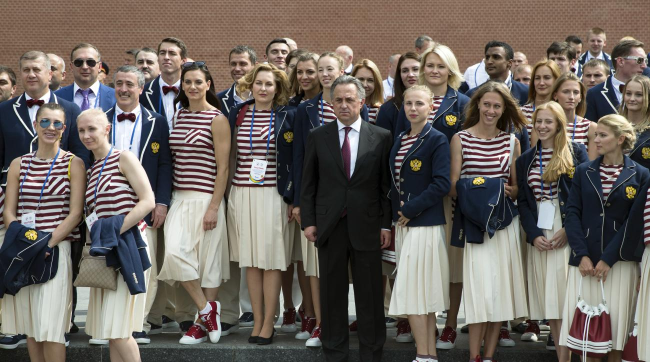 Russia's Sports Minister Vitaly Mutko, center, poses for a photo with Russia's National Olympic team members outside the Kremlin wall, before a meeting with Russian President Vladimir Putin, in Moscow, Russia, Wednesday, July 27, 2016. At least 105 athlet