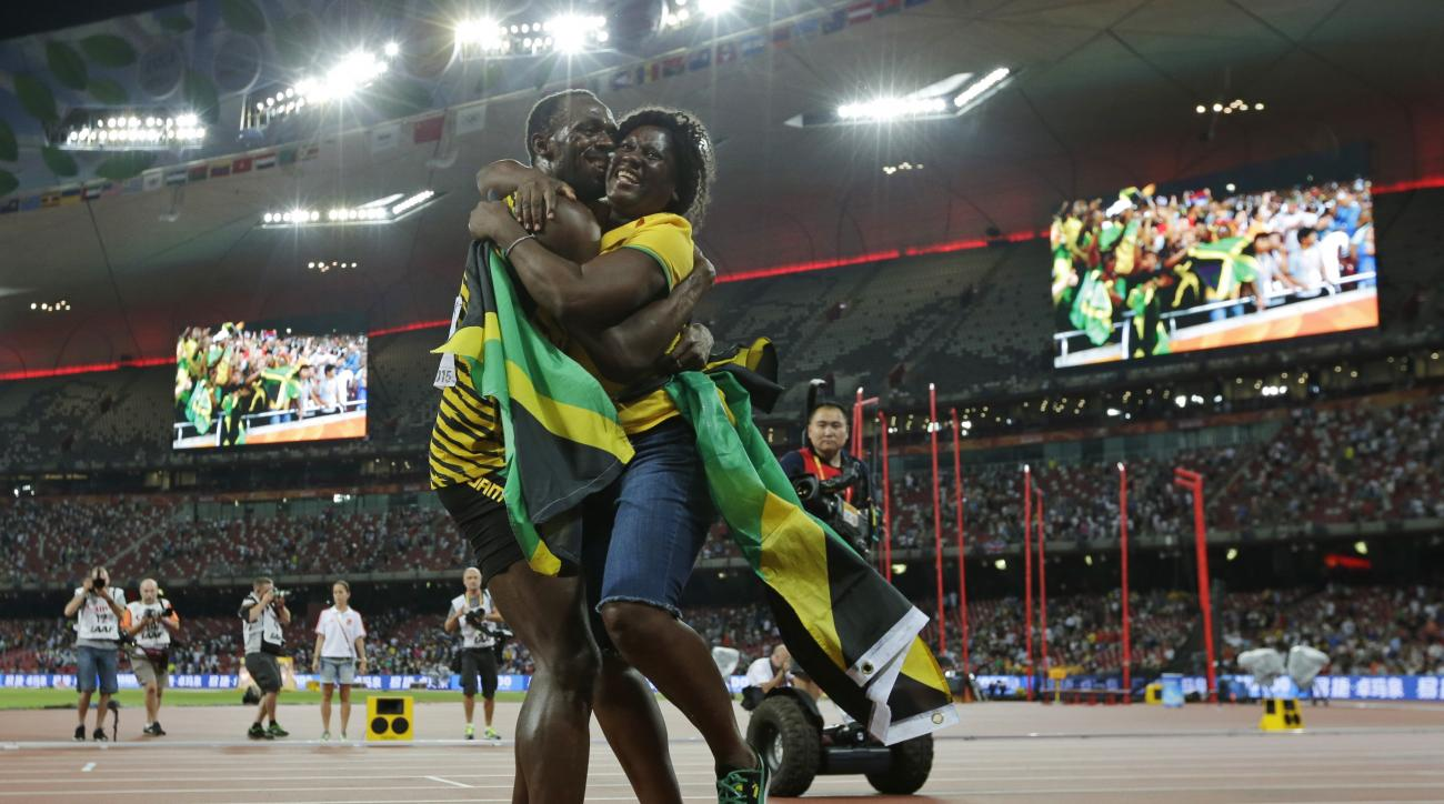FILE - In this Aug. 23, 2015 file photo, Jamaica's Usain Bolt hugs his mom, Jennifer Bolt, after winning the men's 100m final at the World Athletics Championships at the Bird's Nest stadium in Beijing. How does Bolt's mother help the world's fastest man k