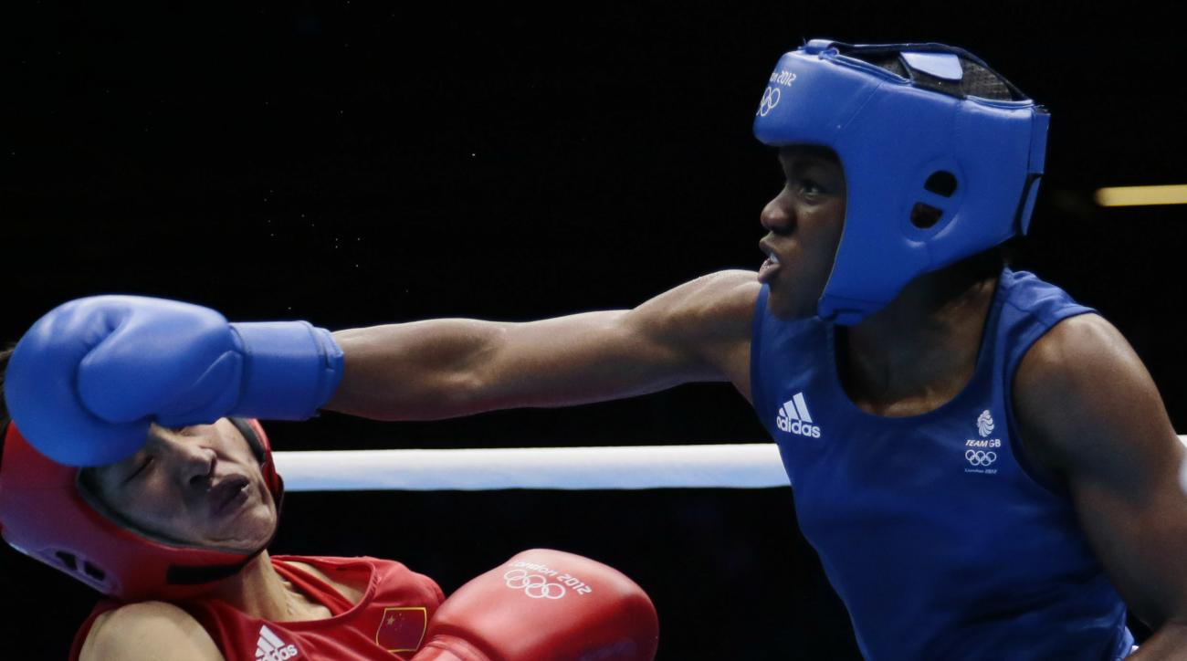 FILE - In this Aug. 9, 2012, file photo, China's Ren Cancan, left, is knocked down by Great Britain's Nicola Adams, blue, during their women's final flyweight 51-kg gold medal boxing match at the 2012 Summer Olympics, in London. The next wave of women's b