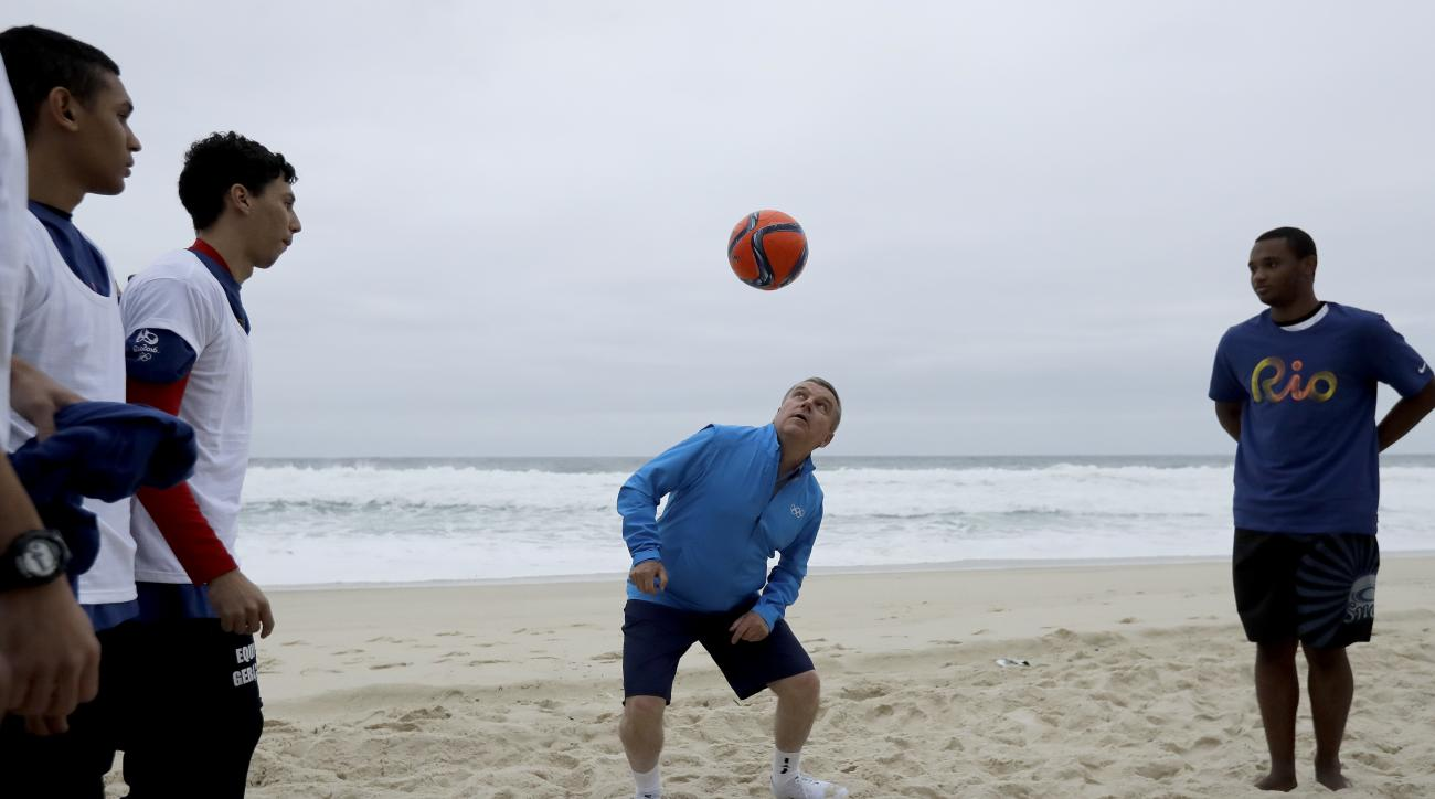 IOC President Thomas Bach passes a soccer ball with kids from a local soccer club on a beach in Rio de Janeiro, Brazil, Thursday, July 28, 2016. (AP Photo/Charlie Riedel)