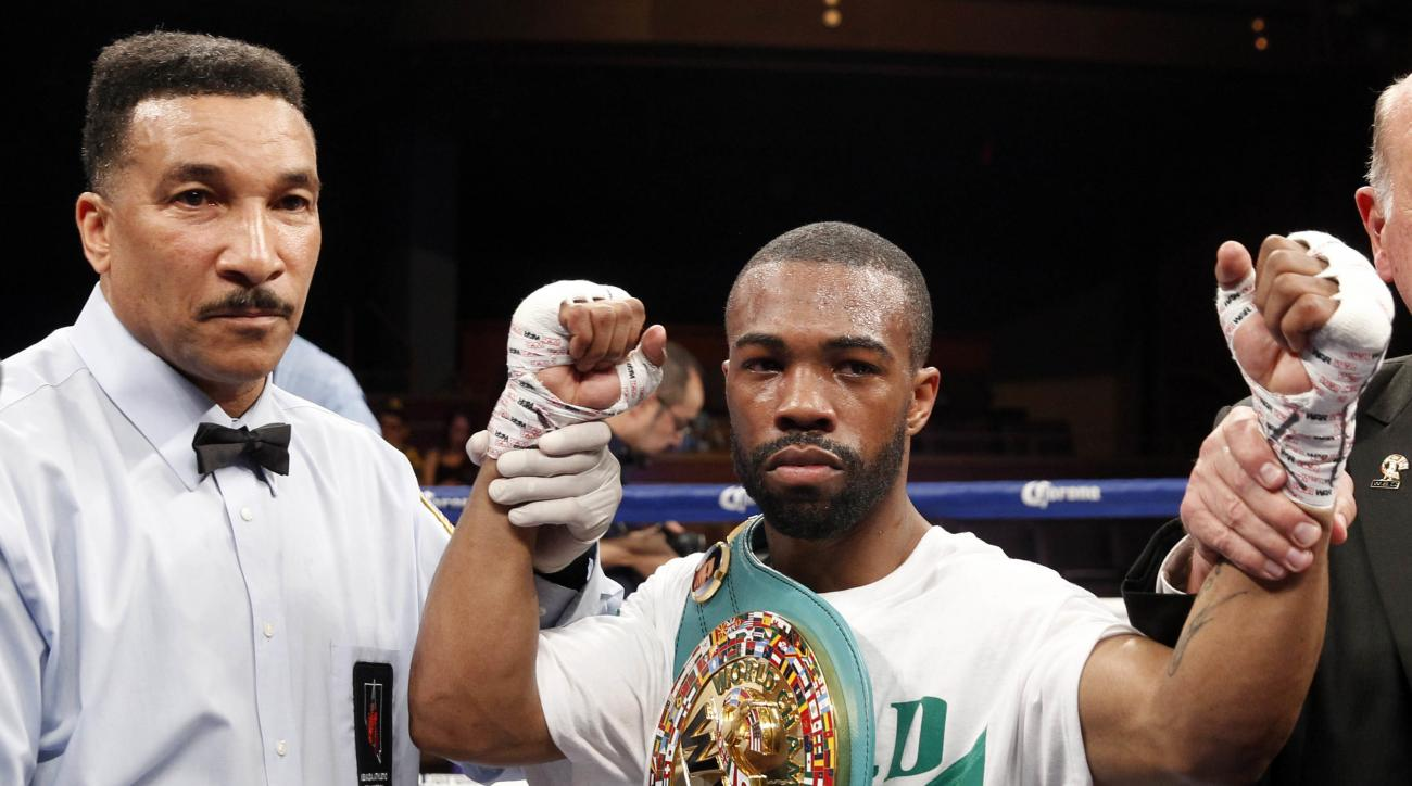 FILE - In this March 28, 2015, file photo, Gary Russell Jr. poses with referee Tony Weeks, left,  after defeating WBC featherweight champion Jhonny Gonzalez, of Mexico, in a title fight in Las Vegas. Gary Russell Jr. collapsed on the night before his Olym