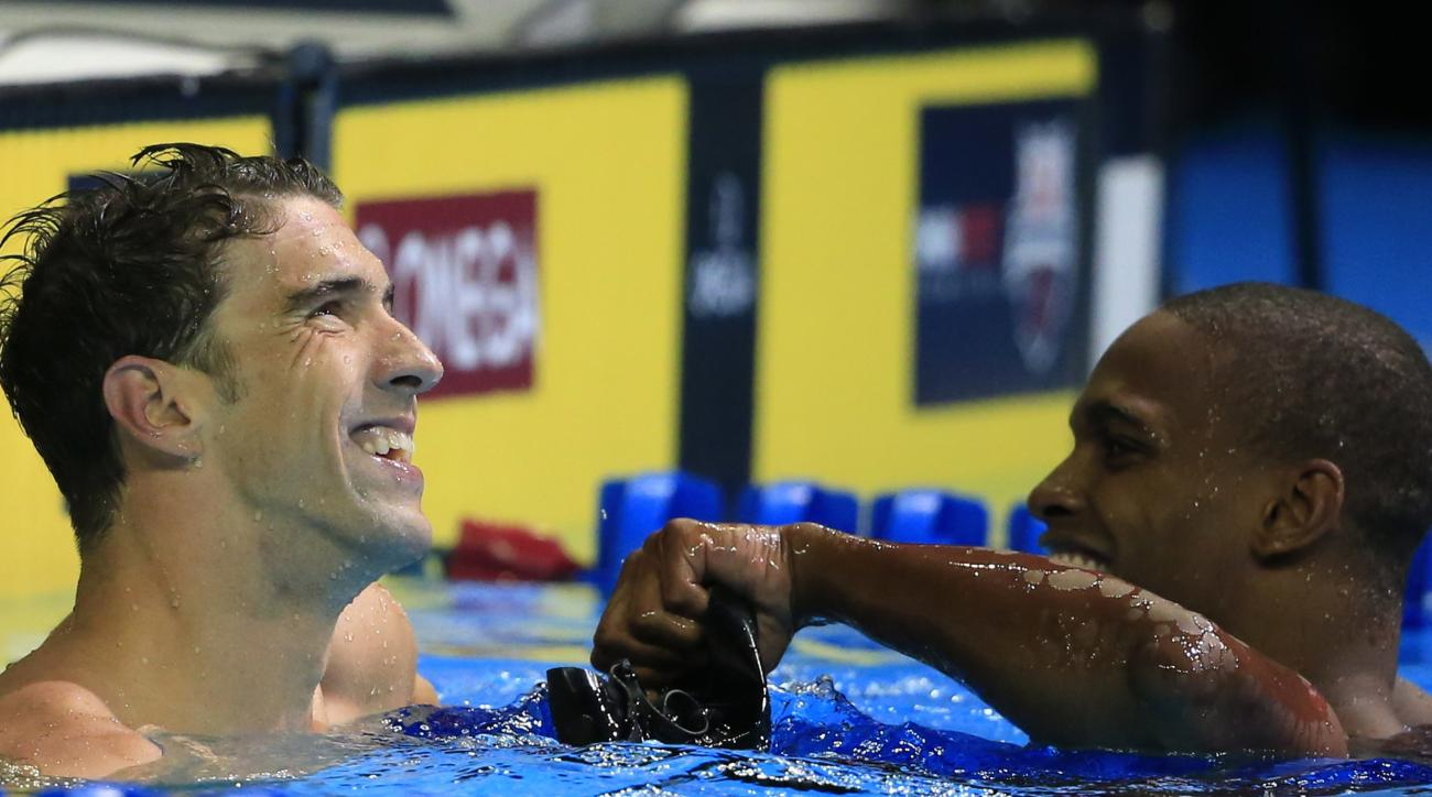 Michael Phelps, left, laughs with Giles Smith, right, after the men's 100-meter butterfly final at the U.S. Olympic swimming trials, Saturday, July 2, 2016, in Omaha, Neb. Phelps won the race. (AP Photo/Nati Harnik)
