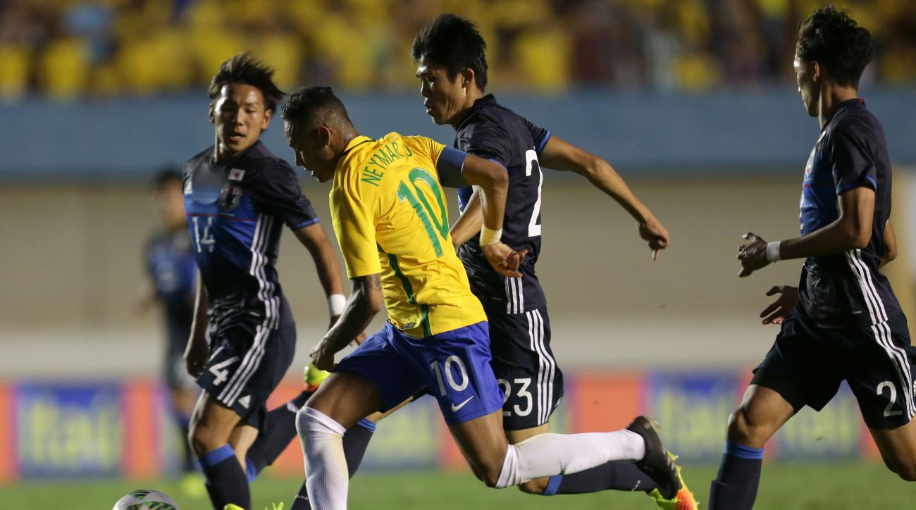 Brazil's Neymar, center, controls the ball past Japan's Sei Maroya, second center, and Japan's Yosuke Ideguche, left, and Japan's Sei Maroya, right, during a friendly soccer game in preparation for the Olympics games, in Goiania, Brazil, Saturday, July, 3