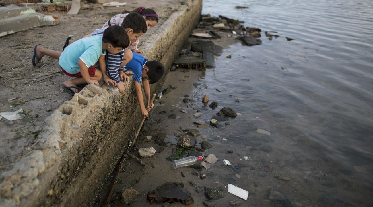 Children try to catch a crab as they play on the polluted shore of Guanabara Bay in Rio de Janeiro, Brazil, Saturday, July 30, 2016. In Rio, the main tourist gateway to the country, a centuries-long sewage problem that was part of Brazils colonial legacy