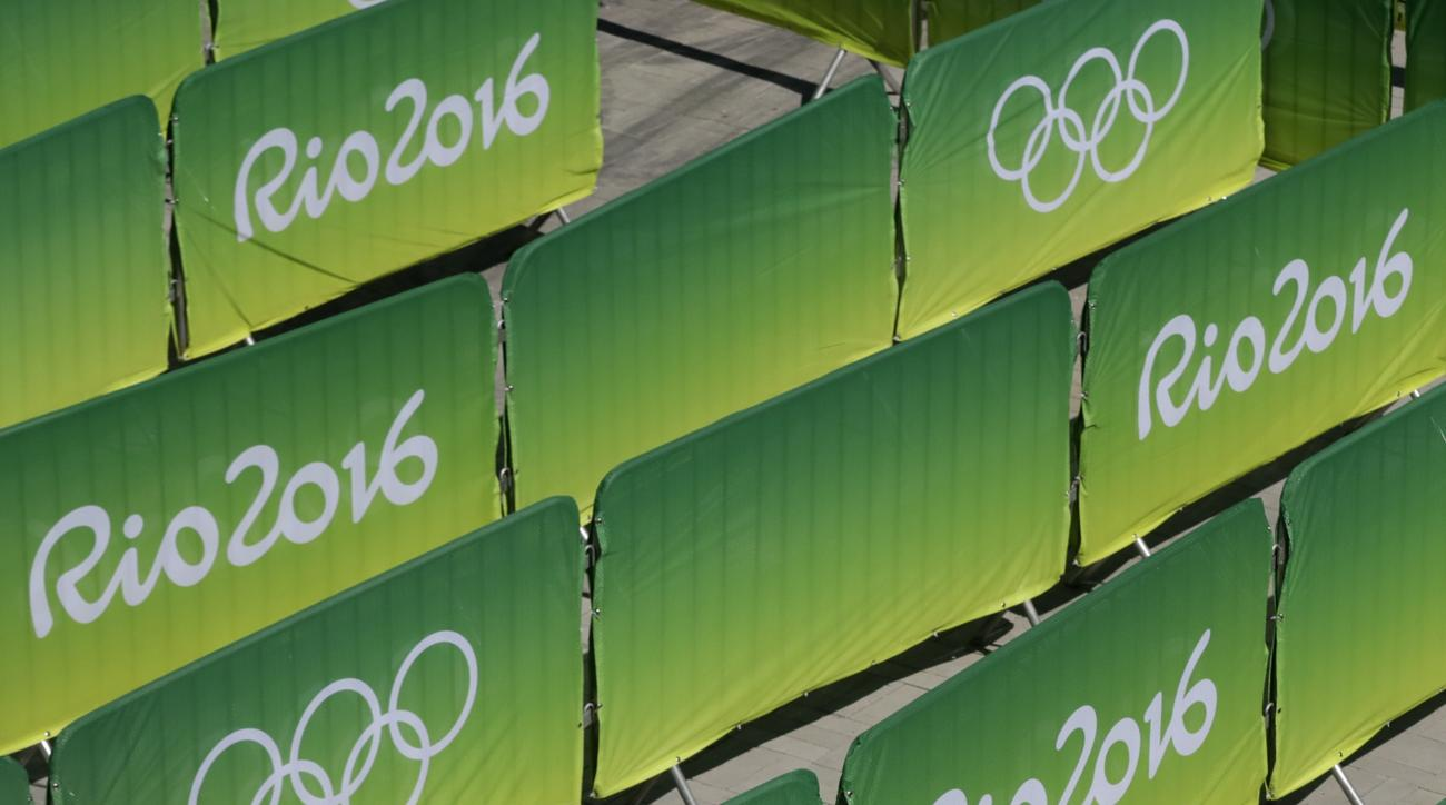 A worker hangs a banner at a ticket entrance booth as preparations continue for the Summer 2016 Olympic games at the Olympic Park in Rio de Janeiro, Brazil, Monday, Aug. 1, 2016. (AP Photo/Charlie Riedel)