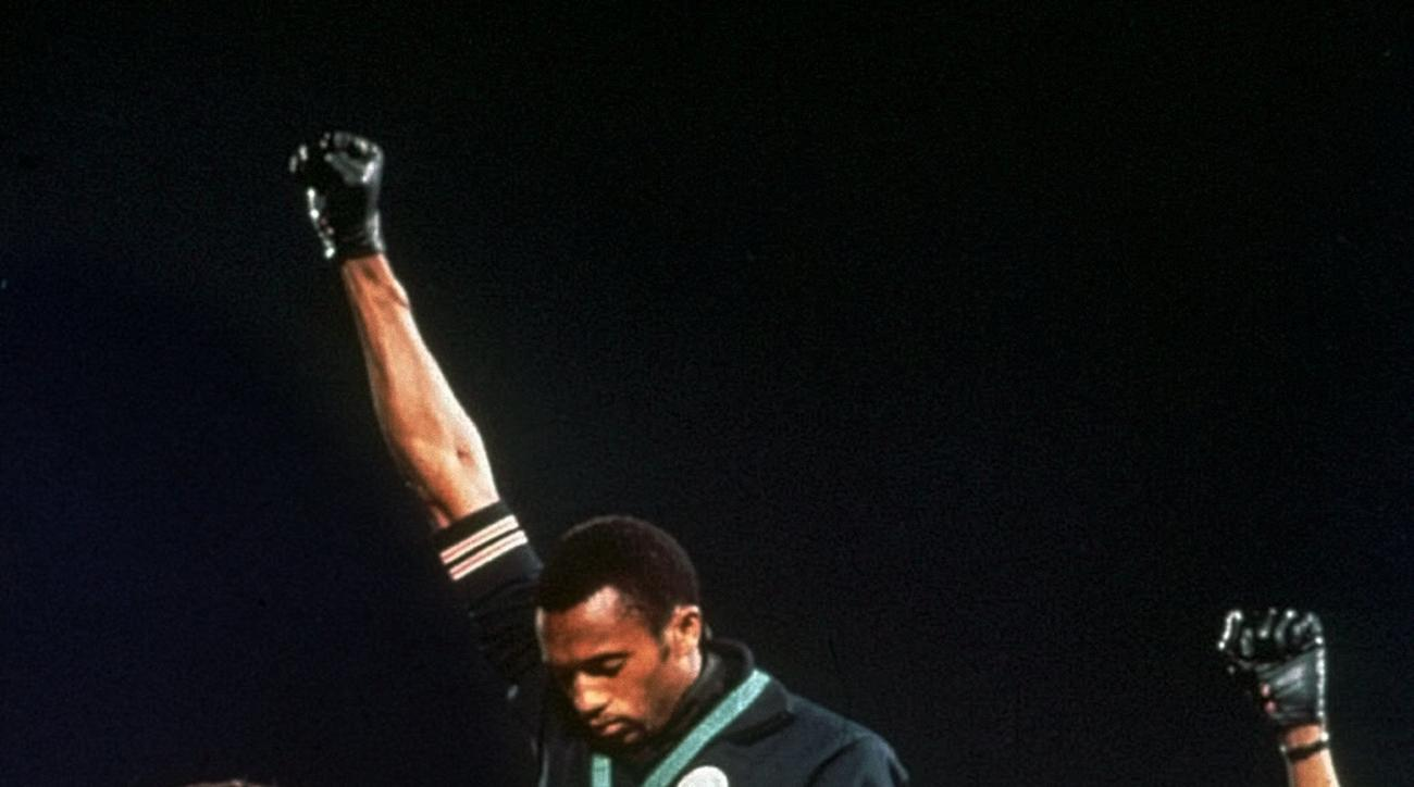 FILe - In this Oct. 16, 1968, file photo, U.S. athletes Tommie Smith, center, and John Carlos stare downward while extending gloved hands skyward during the playing of the Star Spangled Banner after Smith received the gold and Carlos the bronze for the 20