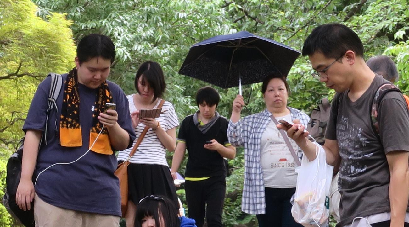 "In this Thursday, June 28, 2016 photo, Pokemon hunters crowd under a green canopy with their mobile phones as they play ""Pokemon Go"" in the Shinjuku Gyoen National Garden in Tokyo. Japanese Olympic gymnast Kohei Uchimura was stunned to receive a 500,000 y"