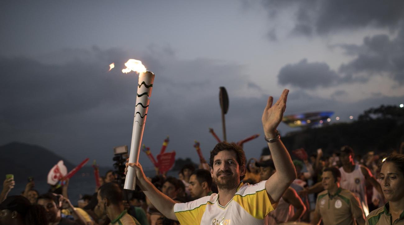 Leonardo Espindola carries the Olympic torch on its way to Rio de Janeiro for the opening ceremony of Rio's 2016 Summer Olympics, in Niteroi, Brazil, Tuesday, Aug. 2, 2016. The three-month torch relay across Brazil will end at the opening ceremony on Aug.
