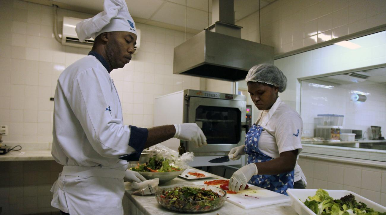 FILE - In this May 6, 2016, file photo, cooks prepare meals during one of many food-testing exercises of the Olympic menu in Rio de Janeiro, Brazil. The caloric intakes for athletes in certain sports as they train for major competitions like what awaits i