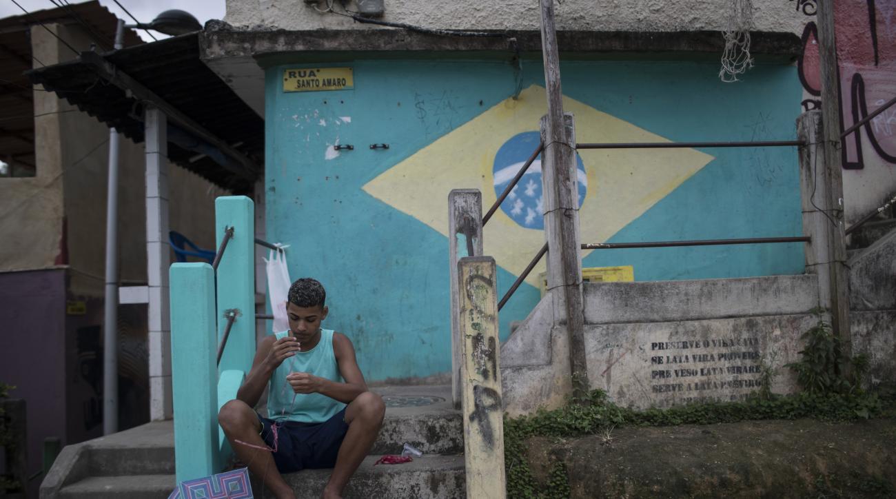 A Boy prepares his kite before flying it at the Babilonia slum in Rio de Janeiro, Brazil, Wednesday, Aug. 3, 2016. The Olympics are scheduled to open Aug. 5. (AP Photo/Felipe Dana)