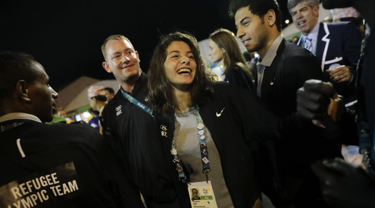 Refugee Olympic Team's Yusra Mardini, center, smiles during a welcome ceremony held at the Olympic village ahead of the 2016 Summer Olympics in Rio de Janeiro, Brazil, Wednesday, Aug. 3, 2016. (AP Photo/Jae C. Hong)