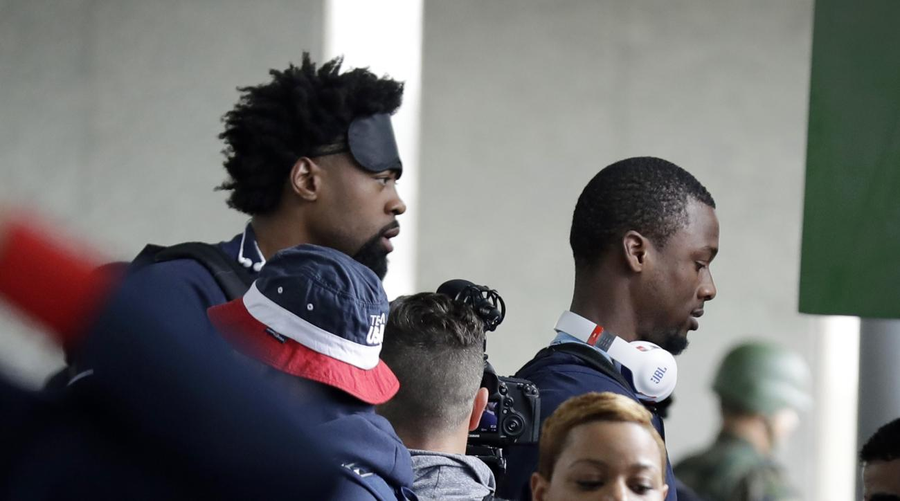 Unites States basketball players DeAndre Jordan, left, and Harrison Barnes board a bus at the airport after arriving at the 2016 Summer Olympics in Rio de Janeiro, Brazil, Wednesday, Aug. 3, 2016. (AP Photo/Charlie Neibergall)